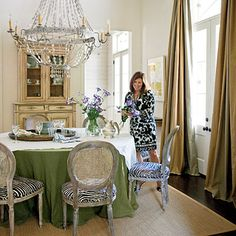 this is so yummy to me.  i love the green table linen, paired with silver in the chandelier and cane chairs.  looks so nice with the camel in the panels and china cabinet.  the white walls just make everything look so fresh.  ~mkw