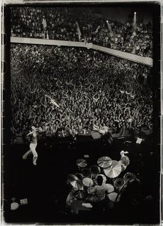 This photo was taken by Michael Zagaris at The San Francisco Winterland in 1976 on the last tour Keith Moon played with The Who,  and considered one of their best ever gigs. As the gig finished, Keith Moon got up and then collapsed over the drum kit-cymbals fell onto the ground in his typical buffon style. Pete Townshend and John Entwistle ended up grabbing him, one by each ankle, and dragging him off stage to tumultuous applause.