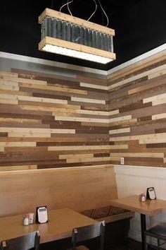 Reclaimed wood wall, wood floor tables, rustic chandelier lighting