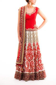 Red and white bridal lehenga with gold highlighting on red threadwork. Thick red velvet borders add elegance and class. The red blouse is completely covered covered in thread work with dainty highlighting around the neckline, waistline, and sleeves.