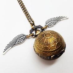 Be the best Seeker Quidditch has seen and catch one of these Golden Snitch working Quartz pocket watch pendant necklaces!  The small pocket watch pendant is available in a choice of ANTIQUE BRONZE WEB, ANTIQUE BRONZE SMOOTH OR SILVER finish and comes on a long 32 nickel free chain.  Each ball pocket watch is embellished with 2 silver plated nickel free wing charms.  I currently have 3 of each silver and bronze web style and 2 smooth bronze style available.  The ball pocket watch measures…