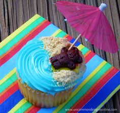 Beach Cupcake SO easy to do and they are perfect for any Summer party! All you do is sprinkle some graham cracker crumbs on one side of a blue cupcake, add your little bear, and finish off with a paper umbrella! That is it! Now, I did make a beach towel out of a fruit roll up, but you don't have to!