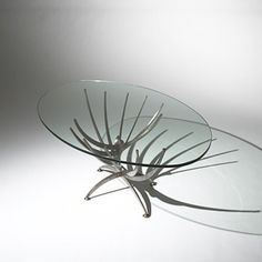 La Table Vrillee (Spiral Table) by Serge Mouille: Created by cutting the twelve supporting arms and two legs into a flat piece of steel, which was then placed in a vice. A lever was attached to the center and four men were required to twist the steel, creating the final radiating shape. #Table #Serge_Mouille