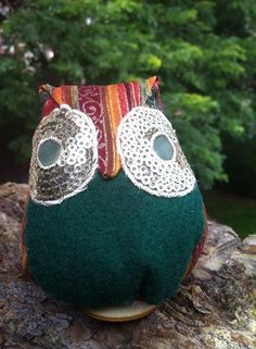 This owl has a silk loop and can be hung as a holiday ornament on a Christmas tree or rear-view mirror or stand freely with its wood base on a fireplace or bookshelf.