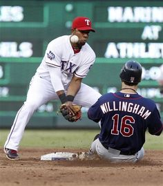 Texas Rangers shortstop Elvis Andrus can't handle the ball as Minnesota Twins' Josh Willingham (16) slides safe into second base on a fielders error during the third inning of a baseball game, Friday, July 6, 2012, in Arlington, Texas. Twins' Joe Mauer scored on the play. (AP Photo/LM Otero)