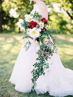 This cascading bouquet, made by Bows   Arrows, holds peonies, roses, scabiosa, clematis, and assorted vines.