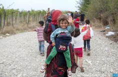 MACEDONIA, GEVGELIJA : Migrants cross the border line between Greece and  Macedonia near the town of Gevgelija on September 6, 2015. Some 5,600  people crossed into Macedonia from Greece on September 4, a jump that  highlights the ever-rising numbers of migrants moving through Europe,  the UN said on September 5. Europe is facing a huge influx on all sides,  with nearly 365,000 migrants and refugees having crossed the  Mediterranean, often in flimsy boats and at the mercy of ruthless human…