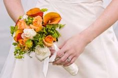 White and orange roses surrounded by orange calla lillies