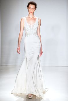 Brides.com: . Sleeveless V-neck sheath wedding dress with sheer corset panel and beaded apliqué detailing, Kenneth Pool