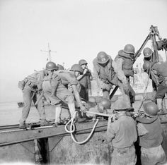 Salerno, 9 September 1943 (Operation Avalanche): American troops place one of their first casualties on board a landing craft.