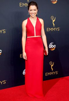 TATIANA MASLANY wears a scarlet Alexander Wang gown with slim cut-outs at the bodice, plus a Lee Savage clutch.