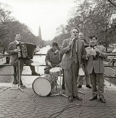 Januari 1970. Singers Johnny Jordaan and Willy Alberti with accordion player Johnny Meyer on a bridge over the Prinsengracht. In the background the Westertoren. © ANP