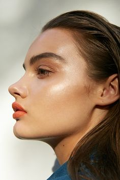 Unkept brows, bronze shimmer, highlighter and orange lips.