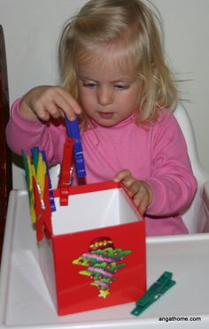 Clothes pins  a box.  Can use slide pins, too. Toddlers may not have strength to open hinged pins.