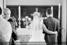 Bride and Groom at alter, child in frame, photograph in black and white.