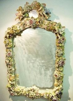A large late 19th century Sitzendorf style oval porcelain framed mirror with all over floral and cherub decoration,