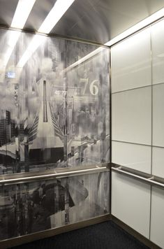 Artwork by Josh Nelson & Dominique Roberge is laminated behind glass in this Elevator Interior Design. Artwork : 76 Olympic Stadium.