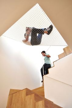 A suspended net provides a hammock over the staircase of this apartment in Porto by architects OODA.