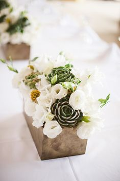 Pretty white, gray and sage green centerpiece in chrome vase - Photo by Jillian Mitchell