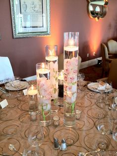 Centerpiece with orchids (or similar flower) in water with floating candles to alternate with higher centerpieces