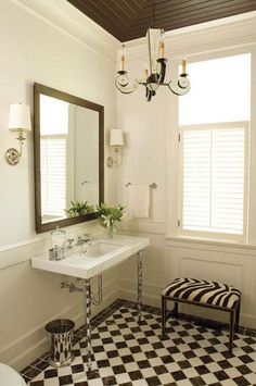 Checkerboard bathroom with a white window shutter.