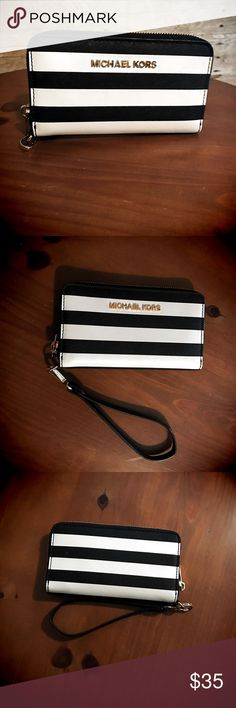 "Michael Kors Saffiano Leather Zip Wallet Michael Kors zip around two-tone black and white Saffiano Leather wallet with golden hardware. Wrist strap, phone pocket (up to 4.7"" smartphone) 3 card slots and one large pocket. Only used this wallet with my black and white MK purse, and was stored in the dust bag with the purse when not in use. Excellent care-excellent buy! EUC!! Michael Kors Bags Clutches & Wristlets"