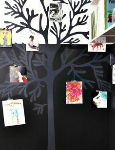 Wall with graphic sticker of a tree. Photos and kids' drawings stuck on the tree.