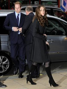 Kate Middleton Trenchcoat Kate Middleton wore a full-skirted black trench coat with knee high suede boots.