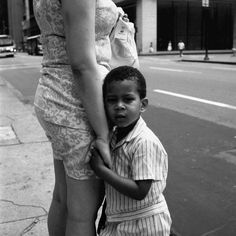 A young boy holding his mom and leaning on her while looking questioningly at the photographer. Undated, Chicago, IL