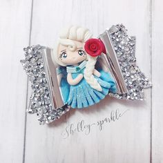Princess Elsa bow. This stunning princess bow is part of my 'Deluxe Princess Range' The bow is made from crystal and diamond embellished fabric finished with a detailed clay princess. Approx size 8.5cm.