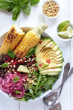 Grilled corn salad bowl with beluga lentils, quick pickled onions, avocado, chili, arugula, pine nuts and fresh basil.