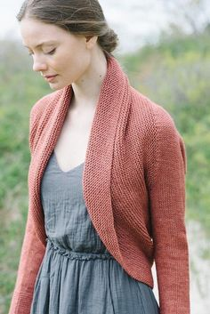 This shrug is worked side to side from cuff to cuff. Sleeves are worked in the round, the back is worked flat, then the band is picked up around selvedge edges of back and worked in the round, making a pretty shawl collar.The sample shown was knit in The Fibre Co. Canopy Worsted, shade Acai. Substitute yarns are recommended below…