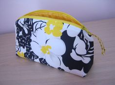 This listing is for a beautiful handmade and fully llined cosmetic/makeup bag in a black and white floral design with a pop of colour!  The outer cotton fabric has pretty yellow highlights to the flowers and is complimented with a yellow zip and a marbled yellow lining. The zip has a small yellow ribon pull.  The pouch is slightly padded to give structure and to help it stand. The top is shaped and the square bottom allows you to stand the bag up and see the contents easily.  Size of bag...