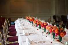 "A bold and colorful arrangements, for a small and very beautiful, Indian wedding, at the Mercier Terrace room at the Ritz Carlton in New Orleans. Flowers included are Hot Pink ""Hot Princess"" Roses, Orange ""Big Fun"" Roses, Orange Dahlias, Orange Snapdragons, Fuchsia Peonies, Orange ""Mambo"" Spray roses, and orange ranunculus, in a turquoise soda shop glass mug."