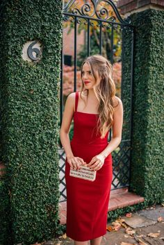 A red-hot slim-fitting dress paired with a metallic clutch.