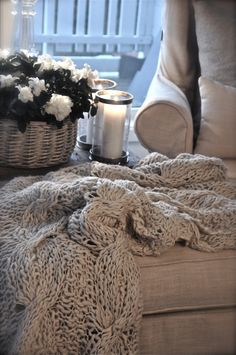 Love these white candles in hurricane glasses, white flowers, and cozy afghan combo for the porch
