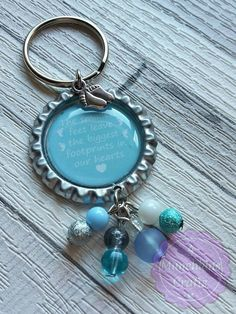 Beaded bottle cap bagtag featuring the wording The smallest feet leave the biggest footprints in our hearts made with a mix of acrylic and glass