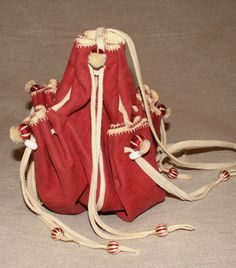 These purses are made from vegetable tanned goat skins that have been dyed using period dyes. They are lined with chamois and are made entirely by hand. The design for this purse comes from a surviving example in the Bayerisches National Museum and is a common style in the 16th and 17th centuries. It hangs from a leather cord and is 7 x 7 inches (18 x 18 cms) when open. The main section is large and lined with soft chamois leather. There are also four outer pockets.  £85