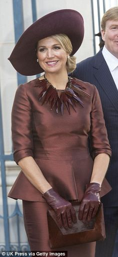 Looking good: Maxima chose a more elaborate burgundy ensemble, complete with a huge neckla...