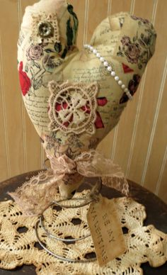Primitive heart on an antique bedspring with a beautiful vintage inspired print.  Features a variety of old laces, an antique gold colored button and strand of faux pearls.