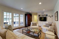 Soft and inviting FAMILY ROOM/DEN-18X16-features recessed lighting. crown molding, built-ins and  a wall of glass with French doors opening to the covered patio and pretty backyard.
