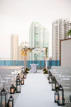 Rooftop wedding at Epic Hotel in Miami, FL: We're loving the aisle lined with rustic lamps and the whimsical woodland wedding arbor.