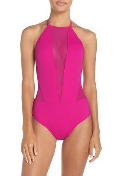 This halter-neck one-piece in fuchsia conceals and reveals with sheer mesh insets through the plunging neck and midriff coupled with an angular open back.