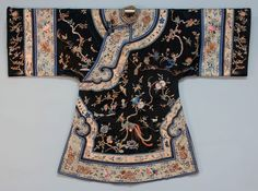 China, silk embroidered robe, black satin embroidered in silk satin stitch and metallic gold, with a variety of birds on flowering branchwork, trimmed in bands of embroidered pale blue satin with metallic gold dragons, embroidered white satin with butterflies, and brocade ribbon, fancy frog closures, lined in pale blue silk, 19th c