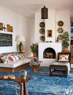 Antique ceramics and colorful fabrics pop against the whitewashed walls of the living room. Textiles from Yastik by Rifat Ozbek, Irving & Morrison, and Robert Kimel Moroccan Berber Rug.