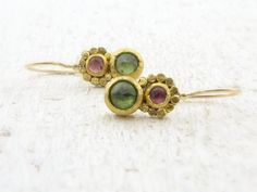 One of a kind earrings feature two gemstones each, one green Peridot and pink Tourmaline , the Tourmaline bezel decorated with 24k solid gold hammered