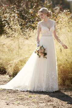 This breathtaking designer bridal gown from Essense of Australia is perfect for a nature-inspired celebration. The illusion lace bodice and sleeves feature elegant corded lace, while the tulle over matte-side Lustre satin skirt carries the lace detailing through to the hem and sweep train. The back zips up with ease under fabric-covered buttons. Accentuate the waist with a detachable 1' grosgrain ribbon belt.' (sp)