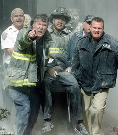Another view of firefighters taking the body of NYC Fire Dept Chaplain Father Mychal Judge out of the Twin Towers after his death(you can see his body but not his head). Father Mychal was inside the atrium of one of the Towers praying when it is believed he had a heart attack (there was a film crew who happened to be documenting life in a fire station). There were no injuries to his body. A gash on his head, according to the Medical Examiner, happened after he died.