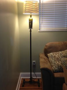 Black pipe, a handful of fittings. A lamp light kit. Empty wine bottle and a cute shade, creates a custom made floor lamp.