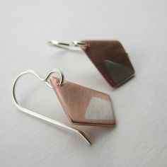 My Asymmetric Earrings combine copper and silver soldered together. Using a rolling mill, Ive fully merged the two metals to create the